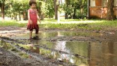 3 years old  girl playing in the puddle of mud Stock Footage