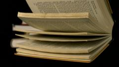 Old book falling on black background, Slow Motion Stock Footage