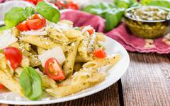 Fresh made penne with basil pesto Stock Photos