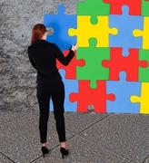 Full length rear view of businesswoman solving colorful jigsaw puzzle against Stock Illustration