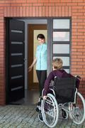 Caregiver inviting woman on wheelchair to nursing home Kuvituskuvat
