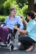 female caregiver talking with handicapped woman on wheelchair - stock photo