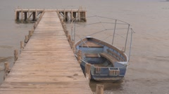 Wooden port with a with blue boat. Stock Footage