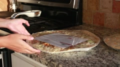 Mother cooking a pizza in her kitchen Stock Footage