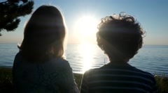 4K WOMAN AND ELDERLY WOMAN WATCH SUNSET OVER LAKE 4K - stock footage