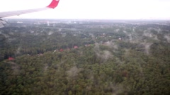 Forest with small cottages under airplane wing, aerial view Stock Footage