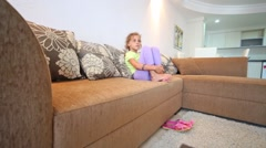 Cute young girl sitting on couch in living room Stock Footage