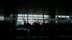 Shadow of people sitting in a dark waiting room area in airport Stock Footage
