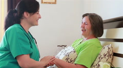 Senior woman talking and laughing with her home caregiver - stock footage