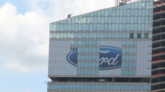Worker cleans outdoor advertising Ford on building Stock Footage
