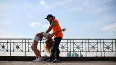 Young pair do acrobatic feat at roof of building in summer day Stock Footage