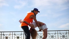 Young man and woman do acrobatic feat at roof of building Stock Footage