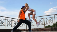 Young man and girl do acrobatic feat at roof of building Stock Footage