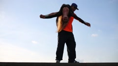Man holds woman on his shoulder and spins at roof of building Stock Footage