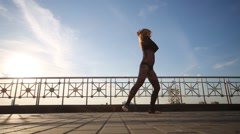 Young woman in black dances at roof of building in sunny day Stock Footage