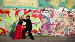 Beautiful couple dancing on street against wall with graffiti Stock Footage