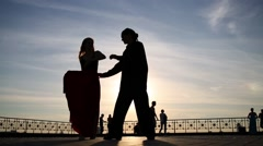Silhouette of beautiful couple dancing on street against sky Stock Footage