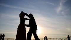 Silhouette of young couple dancing on street against sky Stock Footage