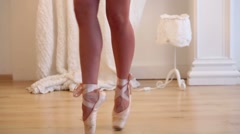 Beautiful female legs in pointes stand on tiptoe in studio Stock Footage
