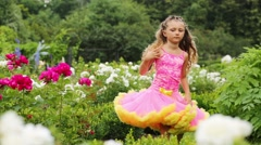 Little girl dressed in gown with puffy hem whirls among flowers Stock Footage