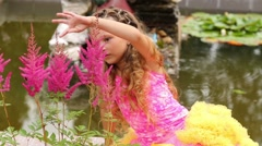 Little girl sits next to pond and looks at flowers and bee Stock Footage