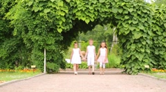 Boy and two girls in white go away on walkway from green gate Stock Footage