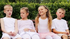 Two boys and two girls in white sit on bench and talk Stock Footage