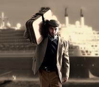 Emigrant with a transatlantic ship behind Stock Photos