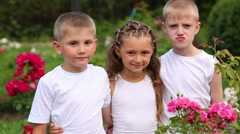 Two boys and girl in white stand among flowers and talk Stock Footage