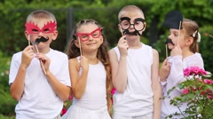 Two boys and two girls stand with masks and pose among flowers Stock Footage