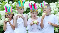 Two happy boys and two girls with red man feathers eat apples Stock Footage