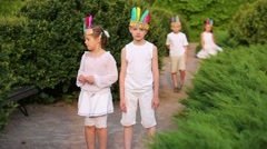 Two boys and two girls with red man feathers hide and jump out - stock footage