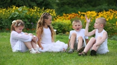 Two boys and two girls in white sit on grass and talk in garden Stock Footage