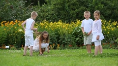 Two boys and two girls in white have fun and rush grass Stock Footage