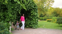 Woman and her little son walk in garden and boy goes towards Stock Footage