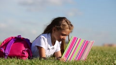 Little girl with pink backpack lies on grass and reads book Stock Footage