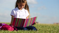 Little girl with pink backpack sits on grass and reads book Stock Footage