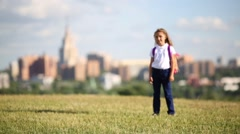 Little girl with pink backpack is marched on green field Stock Footage