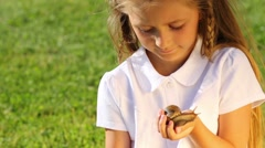 Portrait of smiling little girl in white with large snail in hand Stock Footage
