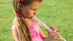 Little girl plays flute on green field at summer sunny day Stock Footage