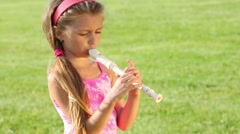 Little pretty girl plays flute on green field at sunny day Stock Footage
