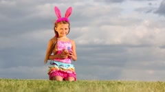 Little girl with hare ears sits and holds basket with eggs Stock Footage