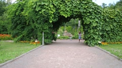 Five happy children run out of arch of green leaves in park Stock Footage