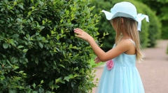 Little girl touches branches and looks into the bush in park Stock Footage