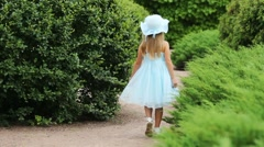 Happy girl in blue dress and hat walks and turns near bushes Stock Footage
