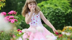 Little girl in white grimaces and smiles near bushes with flowers Stock Footage