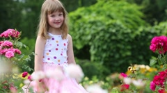 Happy little girl in lush skirt turns near bushes with flowers Stock Footage