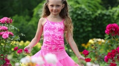 Stock Video Footage of Happy little girl in pink lush skirt turns near bright flowers