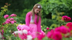 Little girl in pink lush skirt jumps among flowers in summer park Stock Footage
