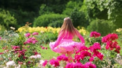 Little girl in pink lush skirt rotates and smiles among flowers Stock Footage